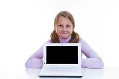 Schulmädchen, das hinter ihrem netbook stationiert Stockfotografie