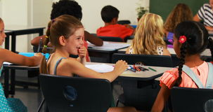 Schulmädchen, das in ihr Freundohr im Klassenzimmer flüstert stock video footage