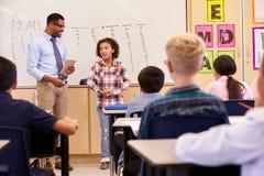 Schulmädchen, das ihren Volksschulemitschülern sich darstellt stockfoto