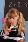 Schulmädchen, das im Klassenzimmer erlernt Stockbilder