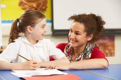 Schulmädchen, das im Klassenzimmer mit Lehrer studiert Stockfoto