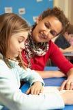 Schulmädchen, das im Klassenzimmer mit Lehrer studiert Stockbilder