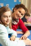 Schulmädchen, das im Klassenzimmer mit Lehrer studiert Lizenzfreies Stockbild