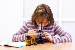 Schulmädchen, das Mikroskop untersucht Lizenzfreies Stockfoto