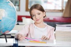 Schulmädchen, das mit Büchern und Kugel am Schreibtisch lächelt Lizenzfreie Stockbilder