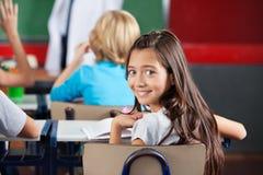 Schulmädchen, das am Schreibtisch im Klassenzimmer sitzt Stockbild