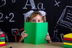 Schulmädchen, das am Schreibtisch mit einem Buch vor dem Gesicht, versteckend nach dem Buch sitzt, umgeben mit Schulbedarf stockfotografie