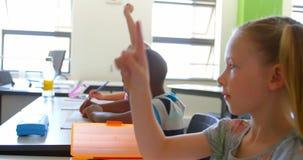 Schulmädchen, das am Schreibtisch sitzt und in der Schule Hand im Klassenzimmer 4k anhebt stock video
