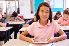 Schulmädchen, das Tablet-Computer in der grundlegenden Schulklasse verwendet stockbild