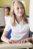 Schulmädchen, das vor einem Schulecomputer studiert Lizenzfreie Stockfotografie