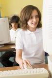 Schulmädchen, das vor einem Schulecomputer studiert stockfotografie