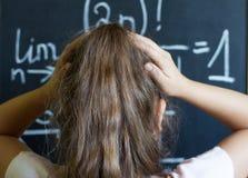 Schulmädchen denkt auf der schwierigen Aufgabe von Mathematik Stockbild