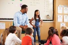 Schulmädchen an der Front der grundlegenden Klasse mit Lehrer stockfotografie