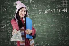 Schulmädchen in der Winterabnutzung, die Studentendarlehen gibt Stockfoto