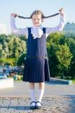 Schulmädchen des kleinen Mädchens, nahm Zöpfe mit ihren Händen auf stockbild