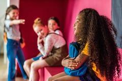 Schulmädchen, die auf ihrem Afroamerikanermitschüler einschüchtern lizenzfreies stockbild