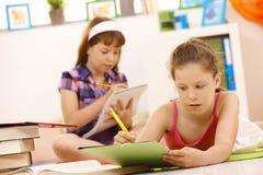 Schulmädchen, die Heimarbeit tun Stockfotos