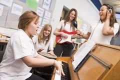 Schulmädchen, die Musikinstrumente spielen stockfotos