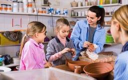 Schulmädchen, die vom Lehrer lernen, Keramik zu machen Lizenzfreie Stockbilder