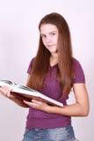 Schulmädchen hält in der Hand größeres Buch Stockbild