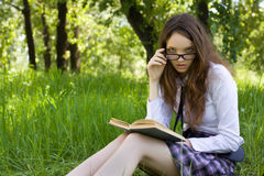 Schulmädchen im Park las Buch Stockfotos