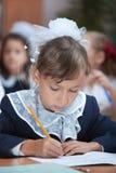 Schulmädchen ist Schreibensübung Lizenzfreie Stockbilder
