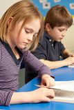 Schulmädchen-Lesebuch im Klassenzimmer Stockbilder