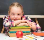 Schulmädchen mit Büchern und Apfel. Stockbilder