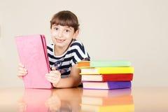 Schulmädchen mit bunten Büchern und Tablet Stockfotos