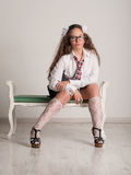 Schulmädchen mit den Gläsern, die auf Sofa sitzen Lizenzfreie Stockfotos
