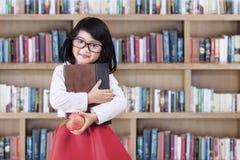 Schulmädchen mit einem Buch und Apfel in der Bibliothek Lizenzfreie Stockfotografie