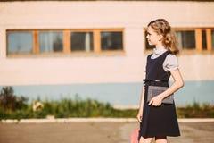 Schulmädchen mit einem Rucksack und einem Buch geht zur Schule stockbild