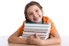 Schulmädchen mit einem Stapel der Bücher Lizenzfreie Stockbilder