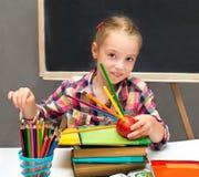 Schulmädchen mit farbigen Bleistiften und Apfel Lizenzfreies Stockbild