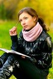 Schulmädchen mit Schreibenbuch und Bleistift Lizenzfreies Stockbild