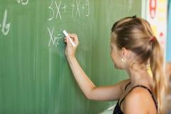 Schulmädchen-Schreiben auf der Tafel lizenzfreies stockbild