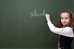 Schulmädchen schreibt auf eine Tafel Stockbild