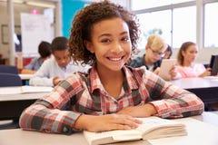 Schulmädchen am Schreibtisch in der Volksschule, die zur Kamera schaut lizenzfreies stockfoto