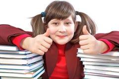 Schulmädchen, schulische Arbeiten und Stapel Bücher Stockbild