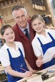 Schulmädchen und Lehrer in der Holzarbeitkategorie Stockfotografie