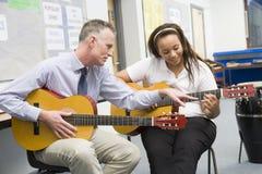 Schulmädchen und Lehrer, die Gitarre spielen Lizenzfreie Stockfotos