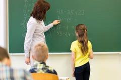 Schulmädchen und Lehrer mit Aufgabe auf Kreidebrett stockfotos