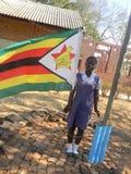 Schulmädchen, welches die simbabwische Flagge bewirtet Stockfotos