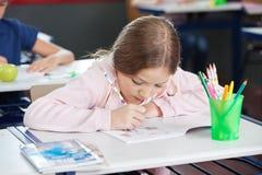 Schulmädchen-Zeichnung im Buch am Schreibtisch Stockfotografie