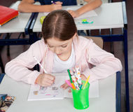 Schulmädchen-Zeichnung am Schreibtisch im Klassenzimmer Lizenzfreies Stockbild