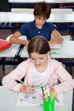Schulmädchen-Zeichnung am Schreibtisch im Klassenzimmer Stockbild