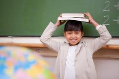 Schulmädchenholding ihr Buch auf ihrem Kopf Stockfotos
