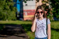Schulmädchenjugendlicher des kleinen Mädchens Sommer in der Natur Sonnenbrille in Form des Herzens Er spricht am Telefon Gefühle  stockbild