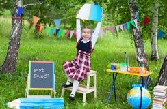 Schulmädchenkinderkindermädchenaufenthalt auf dem Stuhl, der Buchnotizbuch AB hält Stockbilder