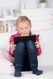 Schulmädchenlesung auf digitaler Auflage zu Hause Lizenzfreie Stockfotos